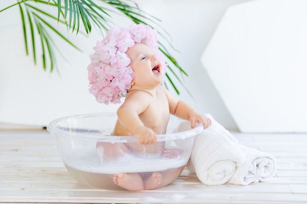 Happy little baby girl washes in a basin with foam and water