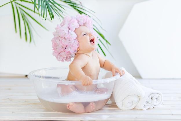 Счастливая маленькая девочка моется в тазу с пеной и водой