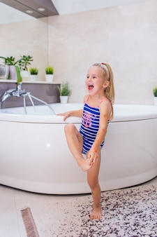 Happy little baby girl in a whetu blue swimsuit staying near bath tub in the bathroom and screaming with smile.