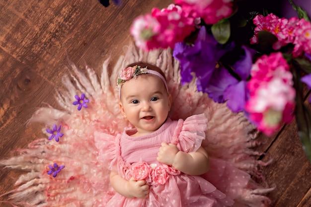 花と幸せな小さな女の赤ちゃん。