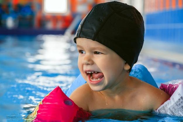 Счастливый малыш в черной резиновой шапочке и розовых надувных рукавах смеется и учится плавать