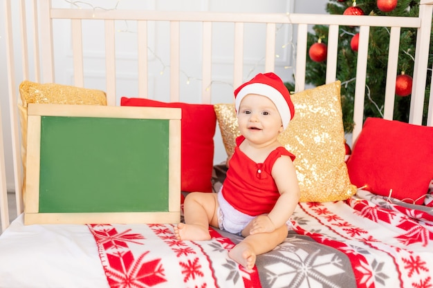 크리스마스 트리 옆에 침대에 앉아 산타 모자에 행복한 작은 아기