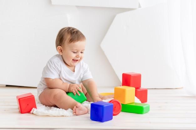 밝은 색의 큐브가있는 밝은 방에 매트에 집에서 놀고있는 흰색 티셔츠와 기저귀에 6 개월 된 행복한 작은 아기
