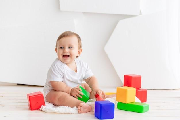 Счастливый маленький ребенок шести месяцев в белой футболке и подгузниках играет дома на коврике в яркой комнате с яркими цветными кубиками.