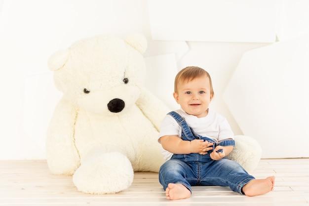 大きなテディベアの近くで家で遊んでいるブルージーンズで生後6ヶ月の幸せな小さな赤ちゃん