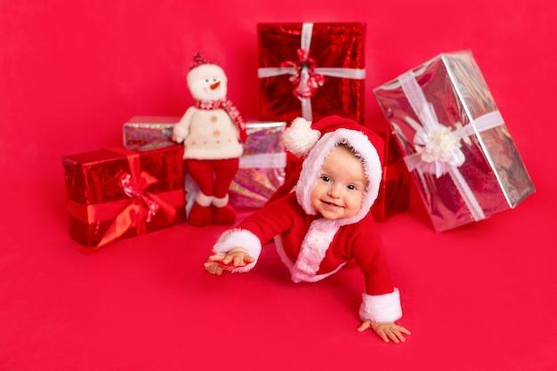 赤い孤立したフォトフォン、テキスト、新年、休日のコンセプトのギフトの近くに座っているサンタの衣装で生後6ヶ月の幸せな小さな赤ちゃん