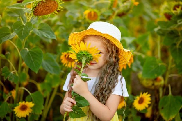 Happy little beautiful girl sniffs a sunflower in a field in summer.