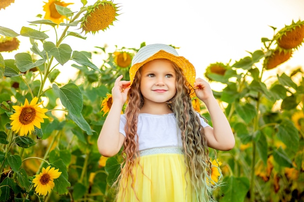 Happy little beautiful girl in a yellow hat in a field with sunflowers in summer