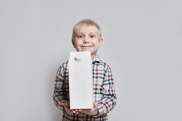 Happy little blond boy is holding a big white carton package. light surface. Premium Photo