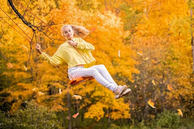 幸せな小さな金髪の白人の女の子が笑顔で公園で秋のロープスイングに乗っています。