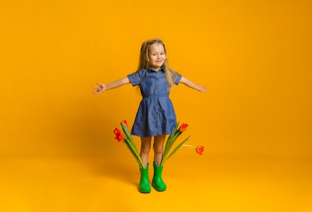 Happy little blonde girl in a blue dress and rubber boots stands with tulips on a yellow wall