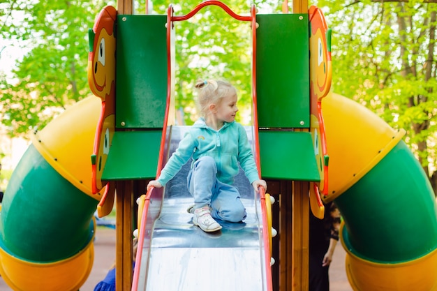 Happy little blonde girl having fun on a playground on a summer day in a sunny city park.