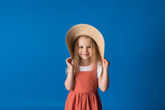 밀짚 모자와 sundress에 행복 한 작은 금발 소녀는 공간의 복사본과 함께 파란색 표면에 서