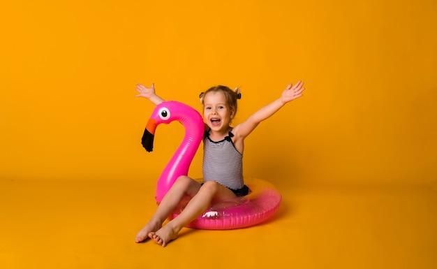 Счастливая маленькая блондинка в полосатом купальнике сидит в розовом надувном круге с фламинго и смотрит в камеру на желтой поверхности с местом для текста