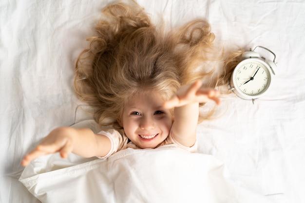 알람 시계와 함께 흰색 침대에 행복 한 작은 금발 소녀, 좋은 아침.