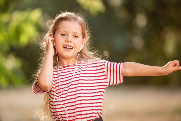 Happy little blonde girl listening to music with headphones, dancing and singing in nature in the park.