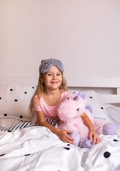 Happy little blonde girl in pajamas sitting on the bed linen on the bed in the room