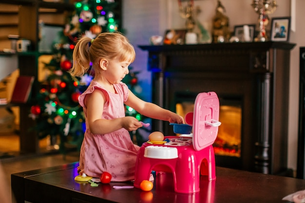 Happy little blonde girl playing near christmas tree with toy kitchen. xmas morning in decorated living room with fireplace and christmas tree.