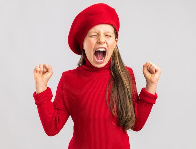 Felice bambina bionda che indossa un berretto rosso che tiene i pugni alzati con gli occhi chiusi isolati sul muro bianco