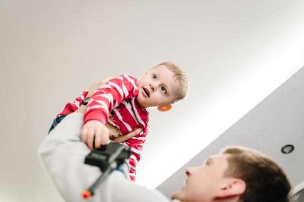 サンタクロースのセーターを着た幸せな男の子とお父さんは、クリスマスを遊んで祝います。家族での休暇を楽しんでいます。メリークリスマス、そしてハッピーニューイヤー。
