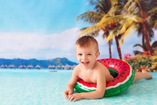 幸せな小さな男の子の赤ちゃんが救命浮輪で海で泳ぐ