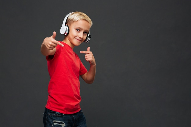 Happy little boy child listening music with headphones.