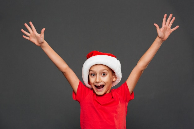 Happy little boy child wearing christmas santa hat