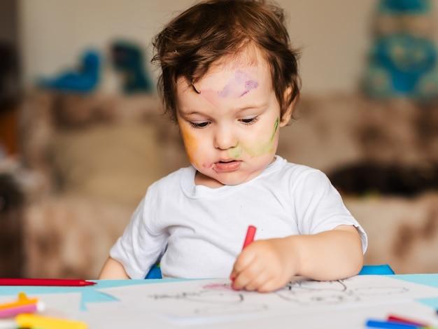 幸せな小さな男の子がアルバムに色鉛筆で描く