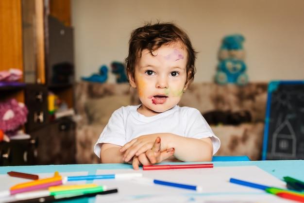 幸せな小さな男の子は一枚の紙にカラフルなマーカーで描く