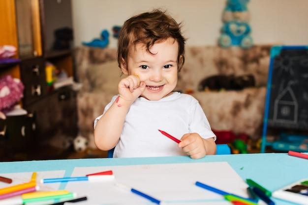 幸せな少年が紙にカラフルなマーカーで絵を描く