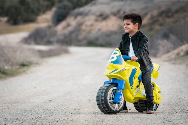 A happy little boy driving a toy motorcycle, dressed in a leather biker jacket on a country road