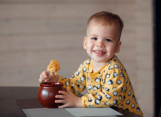 Happy little boy eating honey