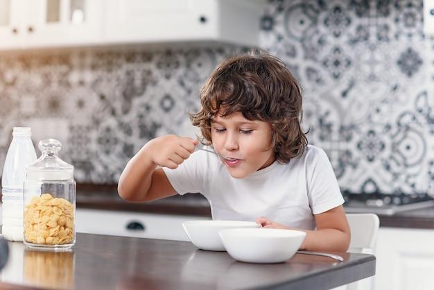 幸せな少年は、キッチンでコーンフレークと牛乳の健康的な朝食を楽しみながら食べます。
