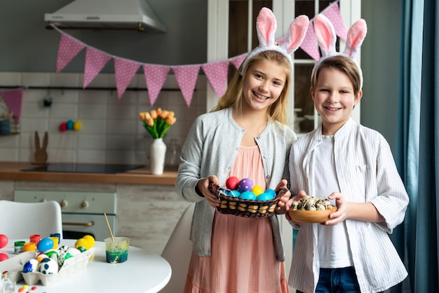 Happy little boy and girl wearing in bunny ears standing and holding a basket with colorful easter eggs