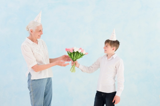 Happy little boy giving tulip flowers bouquet to his grandmother against blue backdrop