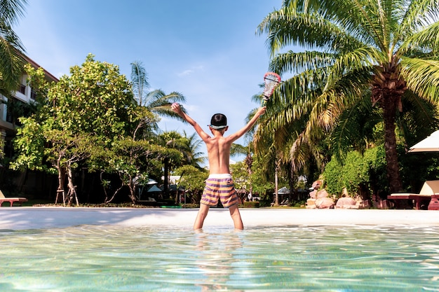 Happy little boy hand reaching up and holding ball and racket standing on swimming pool