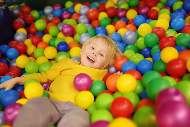 Happy little boy having fun in ball pit with colorful balls