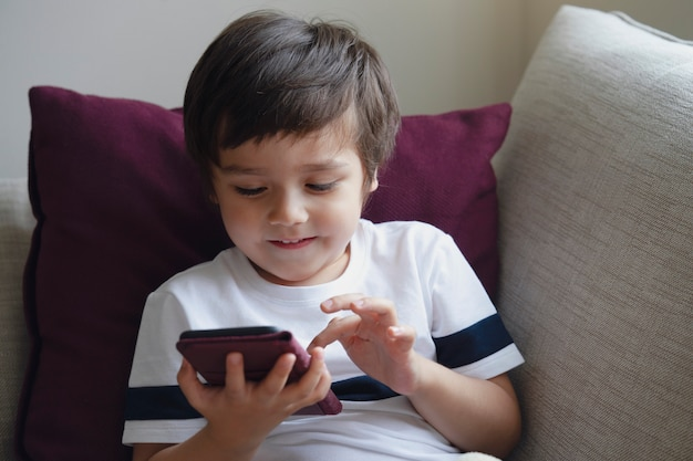 Happy little boy having fun playing game on mobile phone