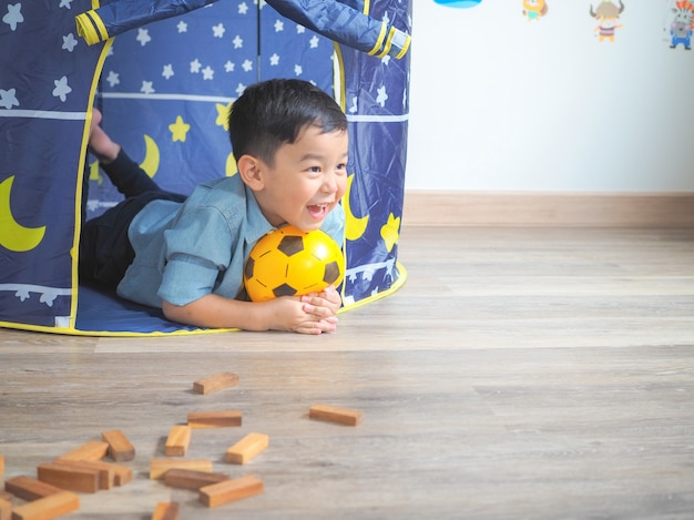 Happy little boy having fun with a play tent at home