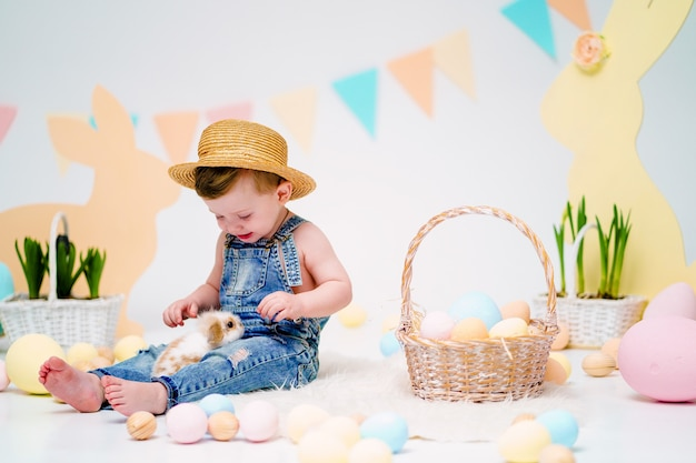 Happy little boy holding cute fluffy bunny near painted easter eggs