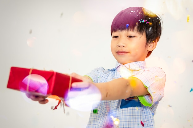 Happy little boy holding a gift box on white background.