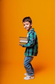 重い本を保持している幸せな少年は黄色の背景を分離しました。教育の概念