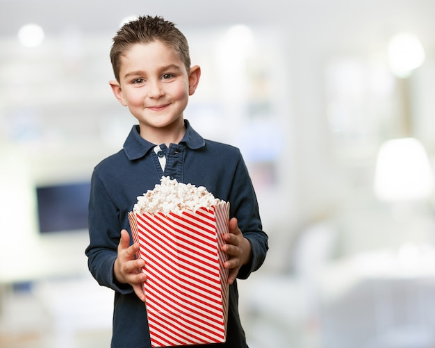 Felice ragazzino in possesso di un secchio di popcorn
