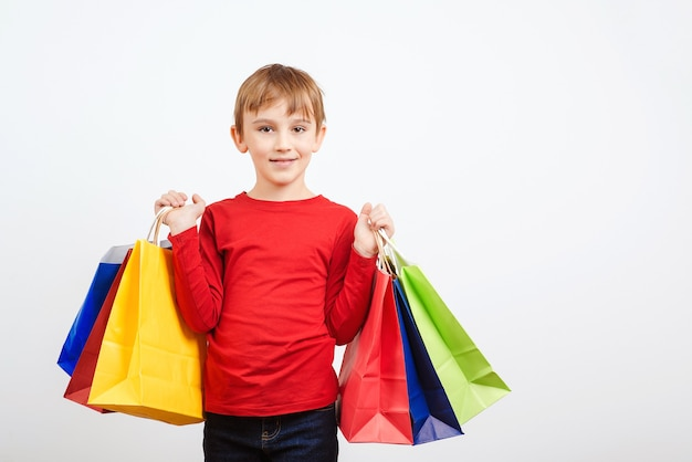 Счастливый маленький мальчик, держащий хозяйственные сумки.