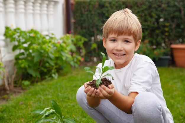 Счастливый маленький мальчик держит в руках почву с зелеными растениями