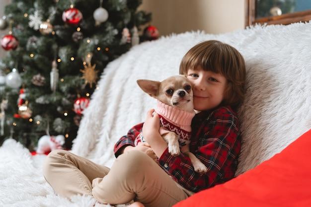 幸せな小さな男の子はクリスマスに犬を抱きしめます