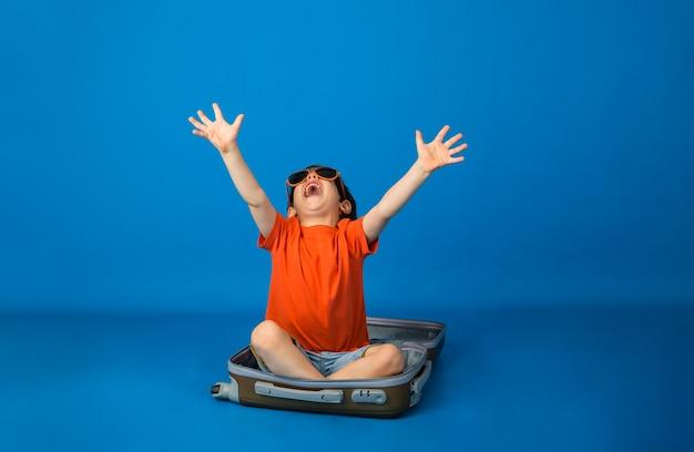 Счастливый маленький мальчик в оранжевой футболке и джинсовой ткани сидит в чемодане на синей поверхности с местом для текста
