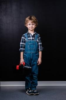 黒いスペースに対して孤立して立っている間、ツールボックスを保持しているデニムのオーバーオールと眼鏡の幸せな少年