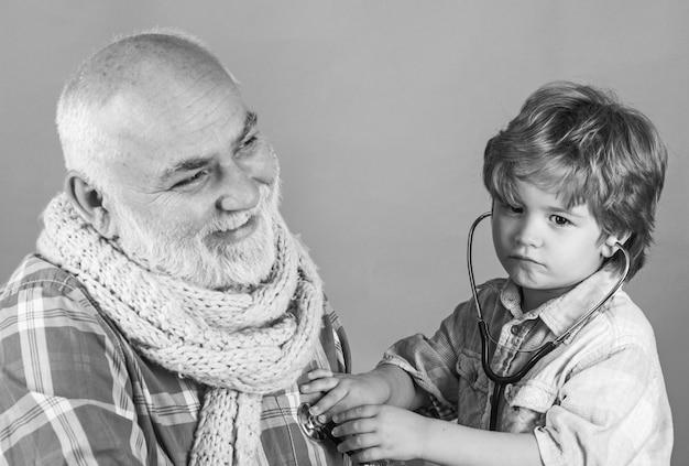 회색 벽에 청진기를 들고 의사 의상에서 행복 한 작은 소년. 아빠와 아이 놀이 의사