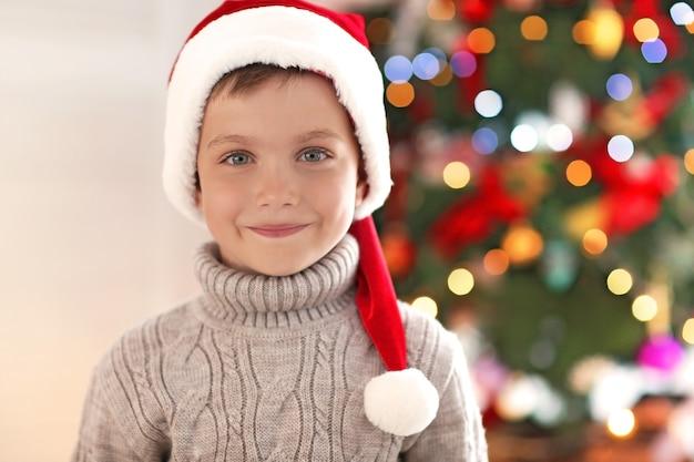 Счастливый маленький мальчик в шляпе санты против размытой елки